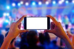 Hands holding a mobile smartphone records colorful live concert with blank white screen stock photo
