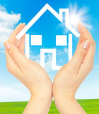 Hands holding model of a house. On nature background Stock Images