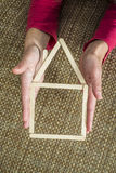 Hands holding model house made of wooden sticks Stock Photos