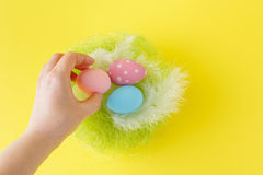 Hands holding modern painted easter egg in a small nest Royalty Free Stock Photos