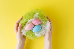 Hands holding modern painted easter egg in a small nest Stock Photo