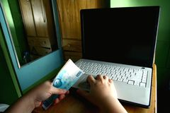 Hands holding money while working on a Computer laptop Stock Photography