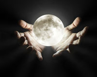 Hands holding moon over black background Royalty Free Stock Image