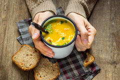 Hands holding mug of soup Royalty Free Stock Image