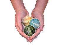 Hands holding nature themed globes. Child hands holding sky, ocean and forest spheres isolated on white background. Conservation, protecting the environment and Royalty Free Stock Photography