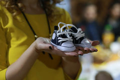 Hands holding newborn baby shoes. Royalty Free Stock Photo