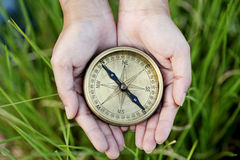 Hands holding a old compass. Hands holding a old style antique compass royalty free stock photos