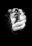 Praying hands. Hands holding onto rosary beads and cross while praying Royalty Free Stock Photo