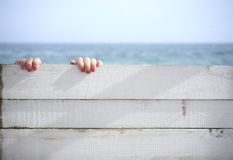 Hands holding onto a wooden wall against the sea Stock Photo