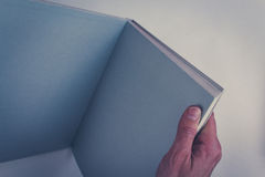 Hands holding open book with blank pages Stock Image