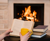 Hands holding open book and cup of coffee near the fireplace Stock Images