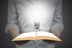 Hands holding open book with light bulb royalty free stock images