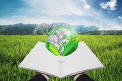 Hand holding opened book with globe with leaves. Element of this image are furnished by NASA. Hands holding opened book with globe with leaves. Element of this stock images