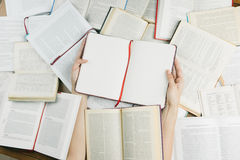 Hands holding opened notebook Among many books. Top view. Get lost in the information. A lot of knowledge royalty free stock image