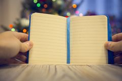 Hands holding an opened notebook on a wooden table against decorated Christmas tree stock photo