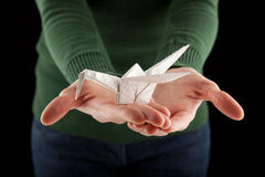 Hands holding an origami crane, focus on the bird Stock Photography