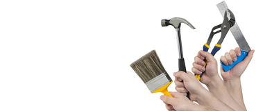 Hands Holding Paintbrush, Hammer, Pliers, and Square Ruler Stock Photo