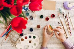 Hands holding and painting easter eggs on rustic table with pain. T and tulips. happy girl preparing for easter celebration and hunt. happy easter concept. flat Stock Photography