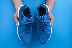 New pair of sneakers in the hands. stock photos