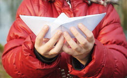 Hands holding a paper boat closeup outside Stock Photography