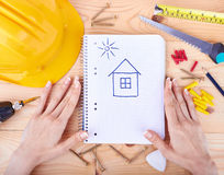 Hands holding paper with drawing a house. Different tools  on a wooden background Stock Photography