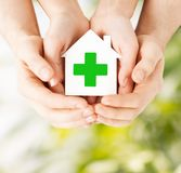 Hands holding paper house with green cross Stock Photo