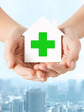 Hands holding paper house with green cross Royalty Free Stock Image