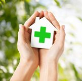 Hands holding paper house with green cross Stock Photography