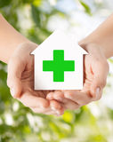 Hands holding paper house with green cross Royalty Free Stock Images