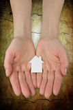 hands holding a paper house icon Stock Image