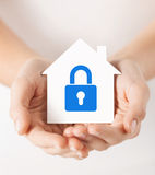 Hands holding paper house with lock. Real estate and family home security concept - closeup picture of female hands holding white paper house with blue lock Royalty Free Stock Photos