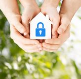 Hands holding paper house with lock. Real estate and family home security concept - closeup picture of male and female hands holding white paper house with blue Royalty Free Stock Images