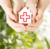 Hands holding paper house with red cross Stock Image