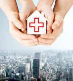 Hands holding paper house with red cross Royalty Free Stock Photography