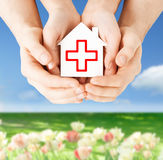 Hands holding paper house with red cross Stock Photos