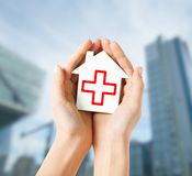 Hands holding paper house with red cross Stock Images