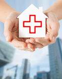 Hands holding paper house with red cross Stock Photo