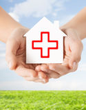 Hands holding paper house with red cross Royalty Free Stock Images