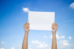 Hands holding paper over the sky. Hand paper on sky background Stock Photography