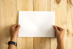 Hands holding paper over wooden background. Empty for text stock photography