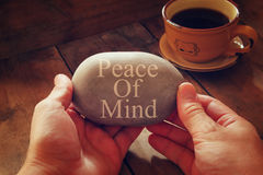 Hands holding pebble stone with the phrase piece of mind Royalty Free Stock Photography