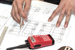 Hands holding pen point to architectural plans project drawing. Architecture hands holding pen point to architectural plans project drawing, architect Stock Photo