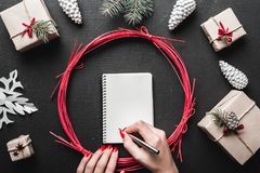 Hands holding pen and writing a letter wish list to santa claus with space for text. Stock Image