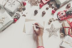Hands holding pencil and writing a letter wish list to santa cla. Us with space for text. merry christmas and happy new year. child hand in pajamas and craft and Stock Photo