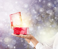 Hands holding and pening a red gift box. Stock Image