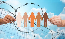 Hands holding people pictogram over barb wire. Crime, imprisonment, refugee and humanity concept - multiracial couple hands holding chain of paper people Stock Images