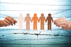 Hands holding people pictogram over barb wire. Crime, imprisonment, refugee and humanity concept - multiracial couple hands holding chain of paper people Stock Photos