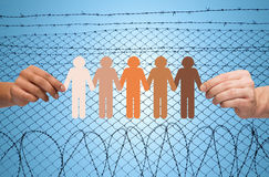 Hands holding people pictogram over barb wire. Crime, imprisonment, refugee and humanity concept - multiracial couple hands holding chain of paper people Royalty Free Stock Image