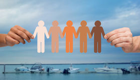 Hands holding people pictogram over boats in sea. Immigration, unity, population, race and humanity concept - multiracial couple hands holding chain of paper Stock Photos