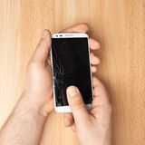 Hands holding a phone with a broken screen. Hands holding a mobile phone with a broken screen over the wooden surface royalty free stock photography